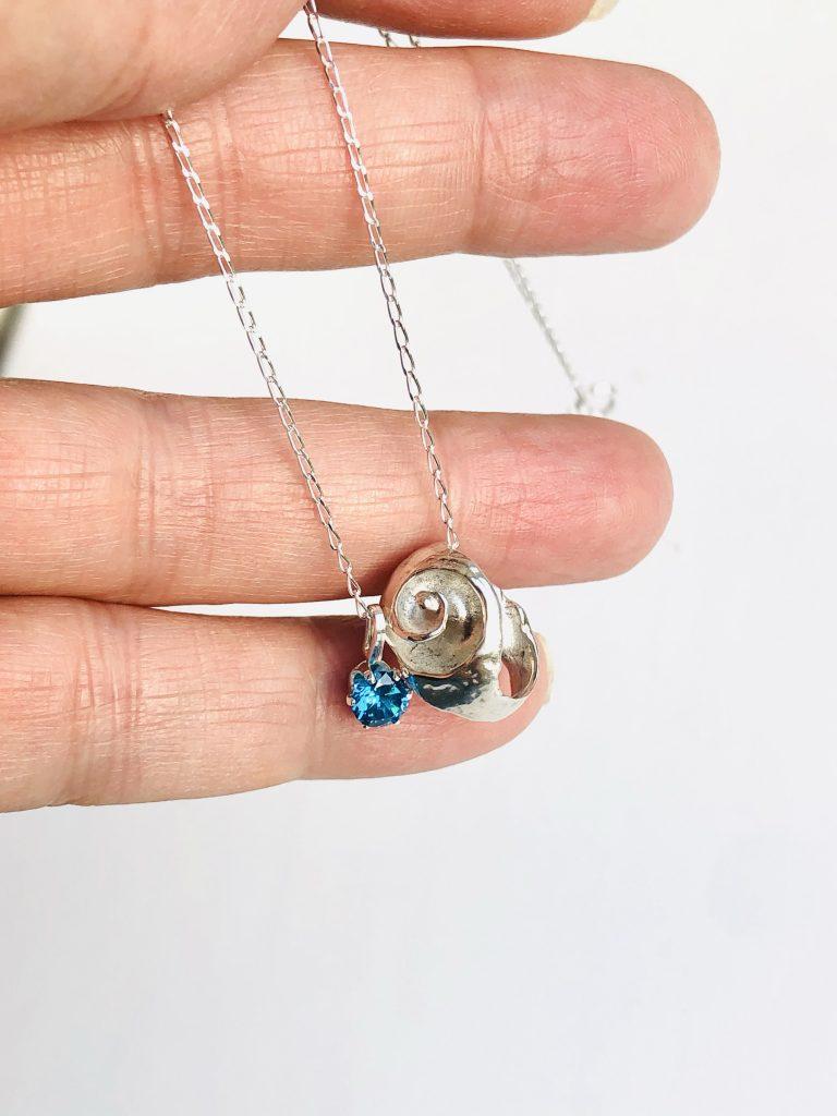medium spiral broken shell with blue topaz december birthstone on a necklace chain